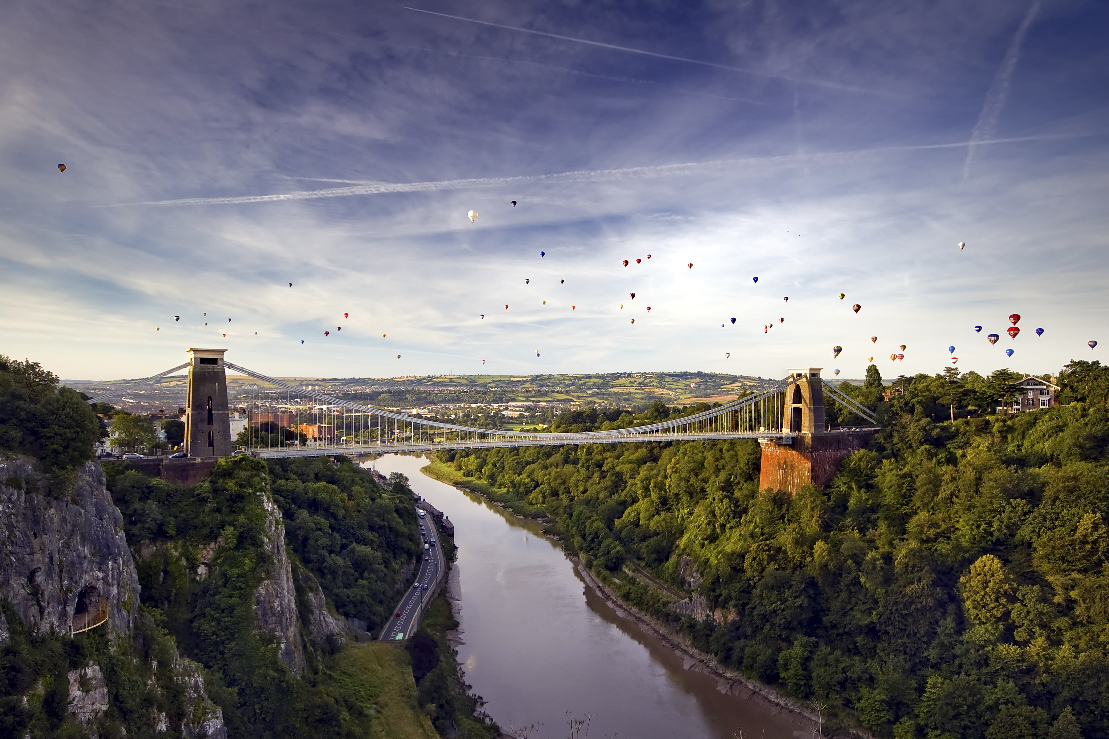 A view up the Avon Gorge of the Clifton Suspension Bridge with a hot air balloon launch behind.