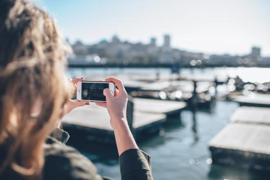 woman takes photo of harbor on iPhone