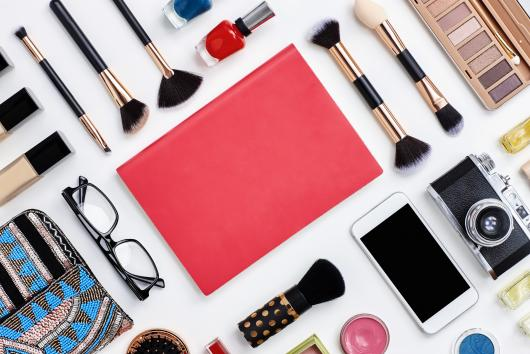 Directly above flat lay shot of pink note book surrounded with various beauty products. Personal accessories are with technologies on white background. The blank space on book can be used for advertisement.