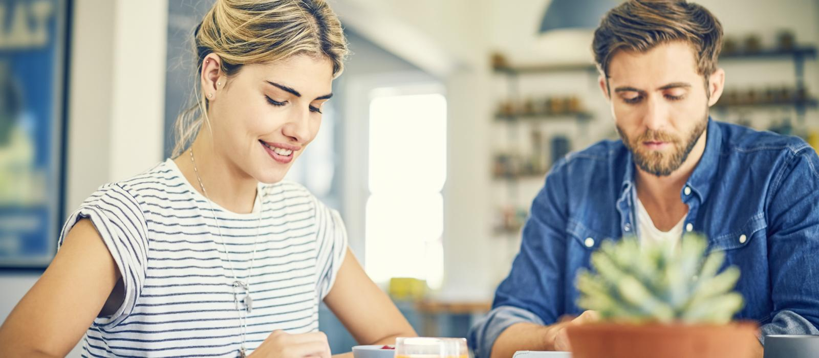 Smiling young woman using digital tablet by man at table. Couple is sitting at table. They are in casuals.