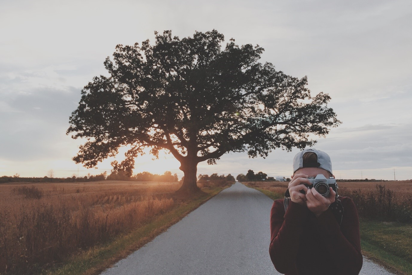 How to take good photos – man takes photo as sun sets