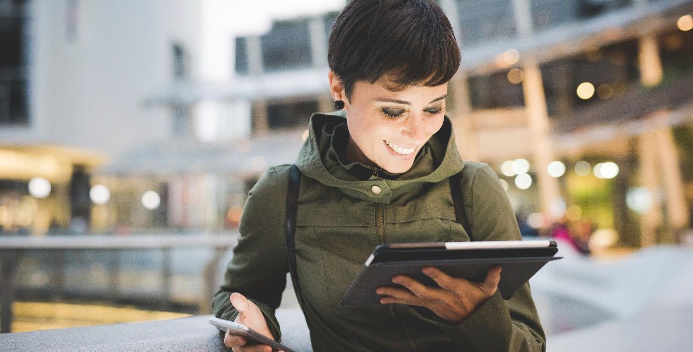 Woman smiles at her iPad while holding phone in other hand.